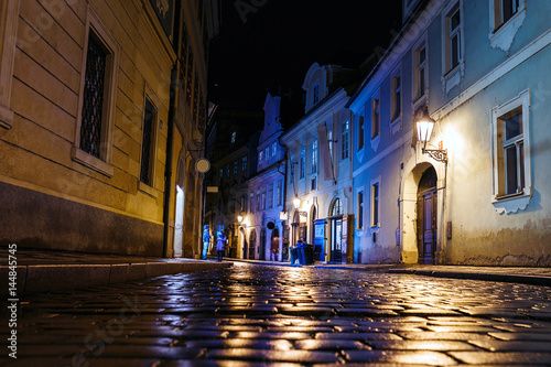 Valokuvatapetti Illuminated cobbled street with light reflections on the pavement in old histori