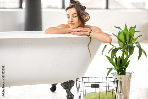 5c6574ecaf8 Beautiful young woman relaxing lying in the bathtube in the bathroom ...