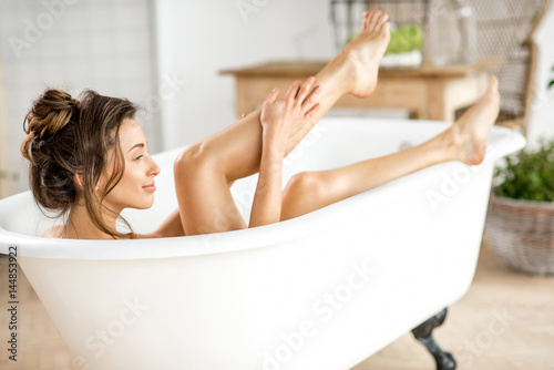 Beautiful young woman taking care about legs lying in the bathtube in the bathro Fototapeta