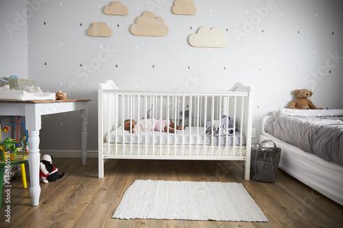 Side View Of Baby Girl Sleeping In Nursery Cot Wallpaper Mural