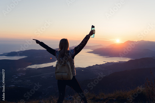 Young woman embracing the sunset while hiking in the mountains Wallpaper Mural