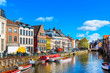canvas print picture - old colorful traditional houses along the canal and boats in popular touristic destination Ghent, Belgium