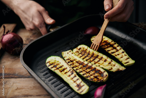 Close-up of female cooking zucchini on grill.