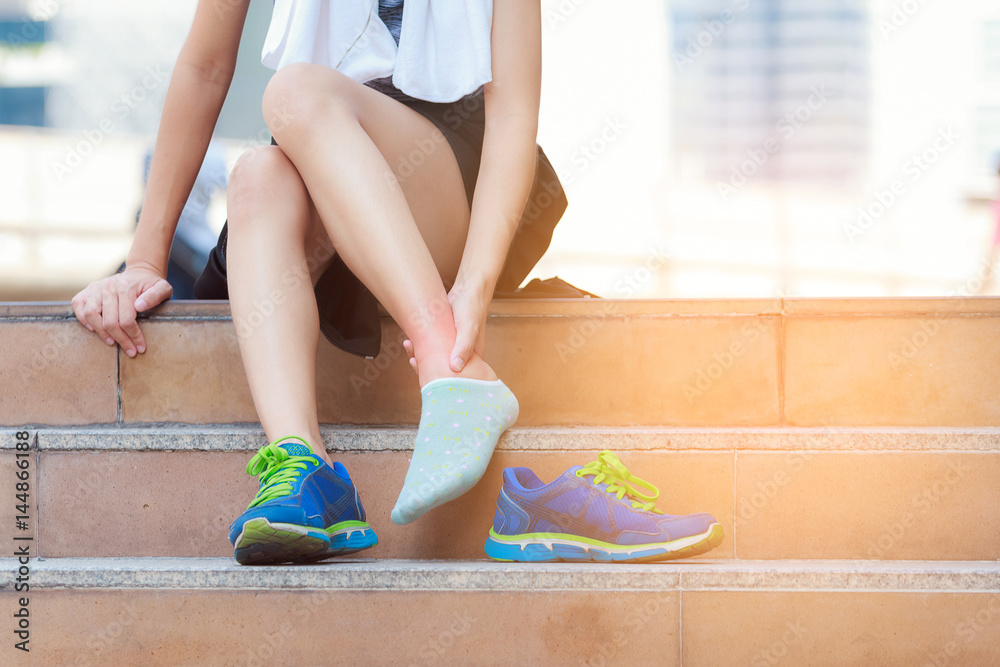 Fototapeta Athlete woman tying running shoes getting ready for jogging