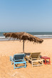 Beach chairs, small table, and an umbrella on a sandy beach in Goa, India