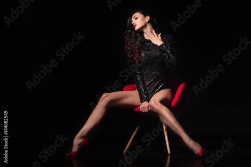 Zdjęcie XXL Portret mody. Idealne, seksowne body i długie nogi młodej kobiety noszącej uwodzicielską bieliznę pozują w zmysłowy sposób w ciemnym pokoju przy czerwonym nowoczesnym krześle