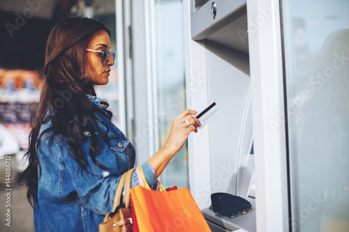 Obraz na plátne Attractive young woman withdrawing money from credit card at ATM