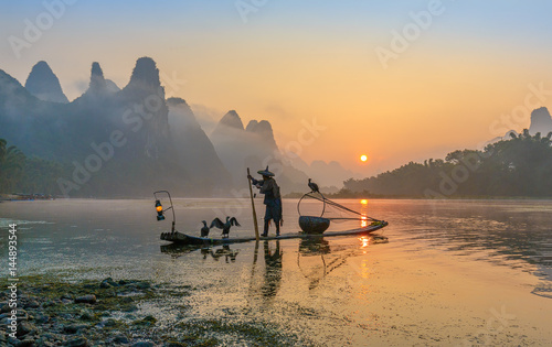 In de dag Guilin Cormorant fisherman stands on the ancient bamboo boat with lamp in the sunrise - The Li River, Xingping, China