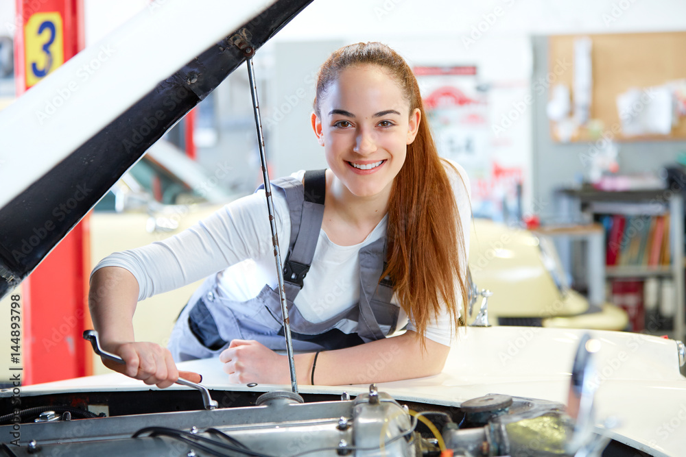 Fototapeta Young female mechanic working on car engine