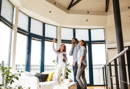 Fotografía  Female Real Estate agent offer home ownership to young couple.
