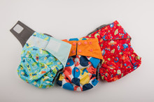 Three Colorful Cotton Diapers Lay On White Background