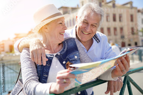 Foto  Senior couple of tourists looking at city map