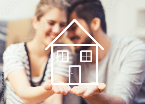 Fototapeta  Young couple holding their new, dream home in hands