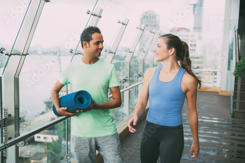 Fotografía  Smiling young man and woman talking on gym balcony