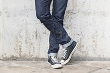 Regular Fit Straight Leg Jeans And Retro Canvas High Top Sneakers On Plaster Wall Background, Selective Focus (detailed Close-up Shot)