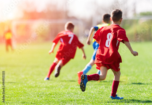 Fotografia, Obraz  Kids soccer football - children players match on soccer field