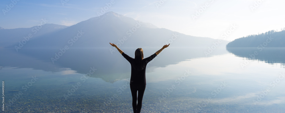 Fototapety, obrazy: The joy of unity with nature. Woman with open arms by the lake on a background of mountains.
