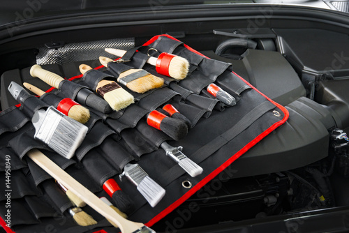 Complect of brushes for cleaning car detailing in front of red car