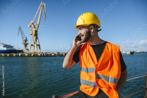 Smiling port worker talking on cell phone