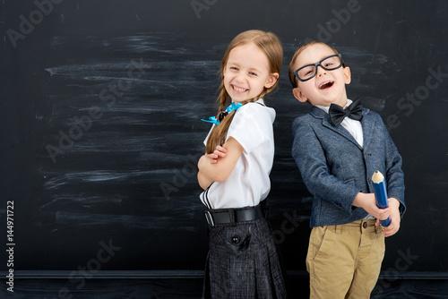 Plakat Mała dziewczynka i chłopiec przeciw blackboard. Koncepcja szkoły