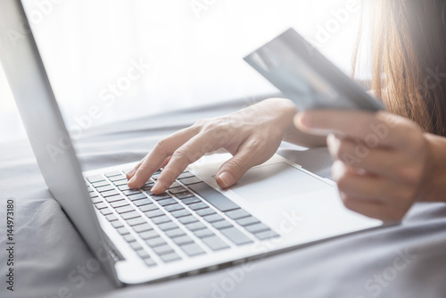 Close up hand using laptop and holding credit card on the bed, Online shopping easy.
