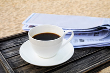 Close Up White Coffee Cup On Wood Table At Sunrise Sand Beach With Newspaper In The Morning
