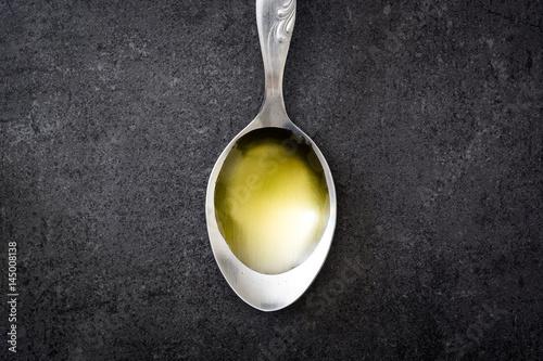 Fototapeta Olive oil on a spoon. Black slate background.   obraz