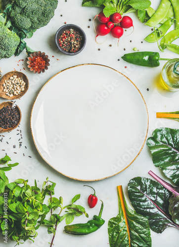 Fotografía  Fresh raw greens, unprocessed vegetables and grains over light grey marble kitchen countertop, wtite plate in center, top view, copy space