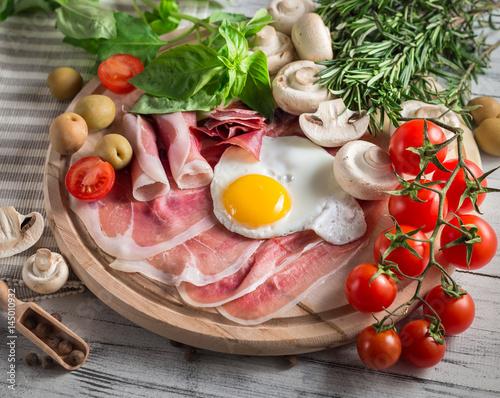 Healthy Mediterranean breakfast ingredients, ham, fried eggs