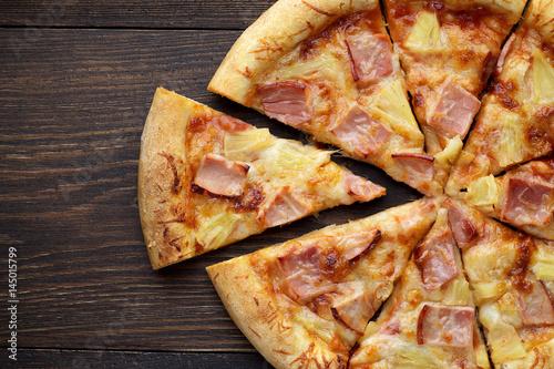 Pokrojona hawajska pizza z szynką i ananasem na ciemnym drewnianym stole.