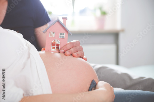 Valokuva  Close up of pregnant belly with small house, concept of new home and familiy