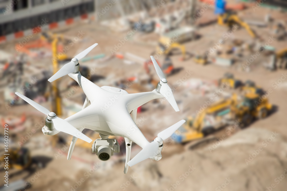 Fototapeta Unmanned Aircraft System (UAV) Quadcopter Drone In The Air Over Construction Site.