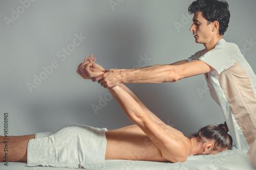 Gay masseur stretches mans body