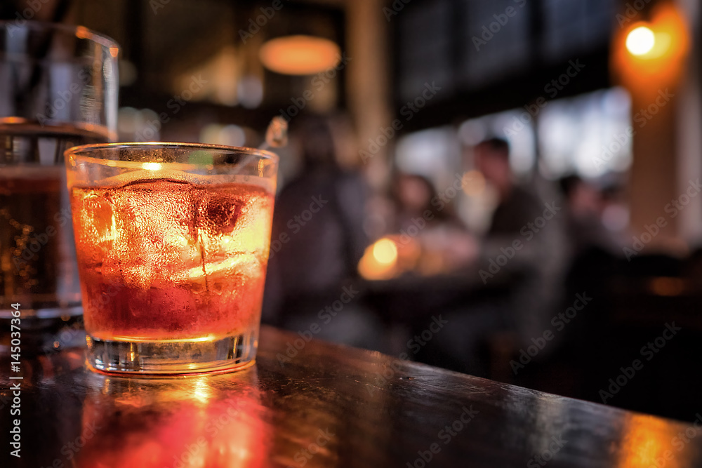 Fototapety, obrazy: Cocktail close up in a bar setting. Blurred people in the background. Selective focus on the icy drink and glass.