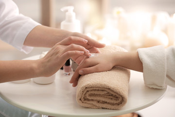 Obraz na płótnie Canvas Young woman undergoing hand treatment in spa salon