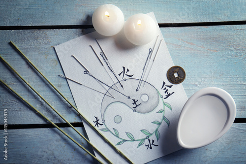 Acupuncture needles with candles and drawing on wooden background Billede på lærred