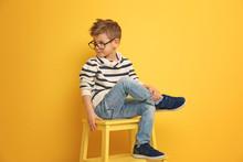 Cute Stylish Boy Sitting On Ch...