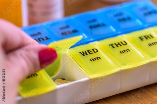 Fotografia  closeup of a woman's hand opening a pill box