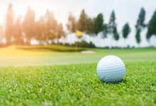 Golf Ball On Golf Course, Flag As Background.