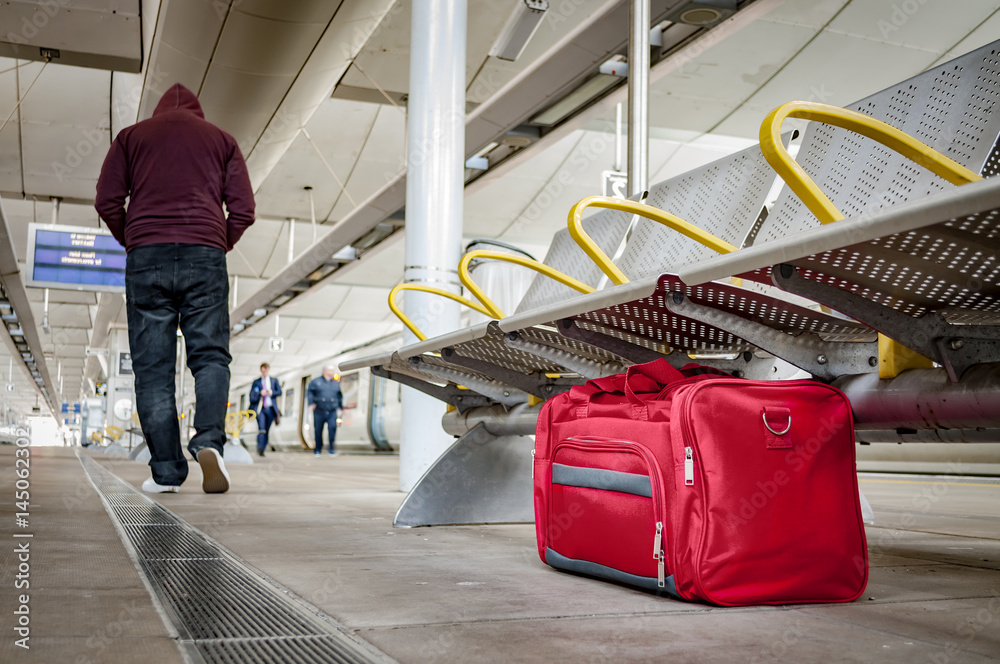 Fototapeta Terrorism and public safety concept with an unattended bag left under chair on platform at train station or airport and man wearing a hoodie walking away from the suspicious item (possibly terrorist)