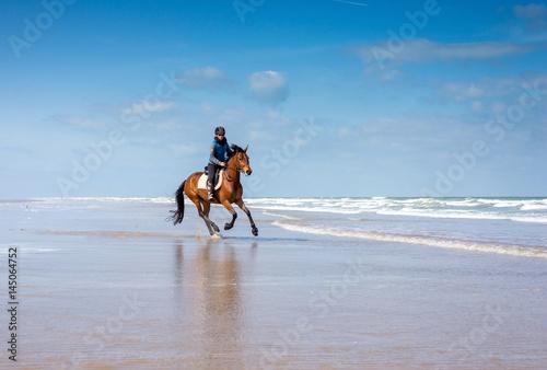 Garden Poster Horseback riding cavalière au galop sur la plage
