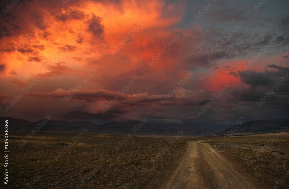 Fototapeta Road path on a desert wild mountain plateau at the background of the hills under a dramatic sunset colorful sky with illuminated red pink purple clouds Kurai Altai Mountains Siberia Russia