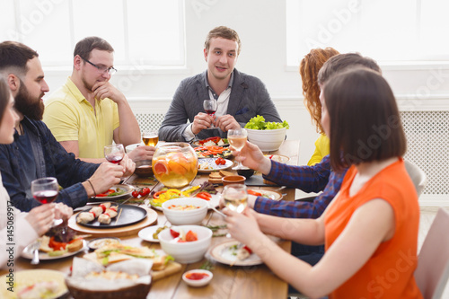 Fotografia  Group of happy young people at dinner table, friends party