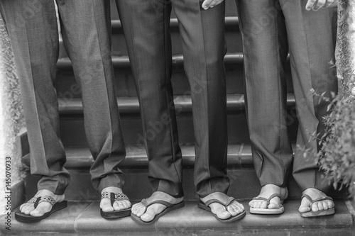 dettaglio piedi di 3 uomini con pantaloni eleganti e infradito