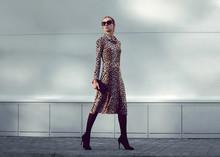 Fashion Woman Model Wearing A Leopard Dress Is Walking In A Evening City