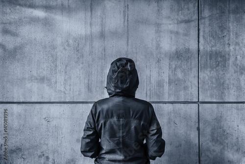 Fotografía  Unrecognizable hooded female person facing concrete wall as insu