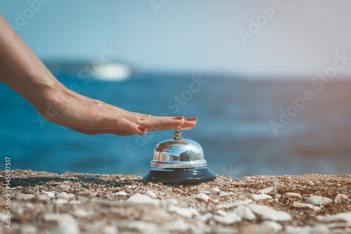 Close up of female hand ringing service bell against the ocean background. Summertime concept.