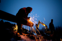 A Worker Grinds A Pipe On The ...