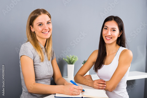 Spoed Foto op Canvas Fitness Woman receptionist of the fitness center and sporty woman having conversation about membership and exercising.