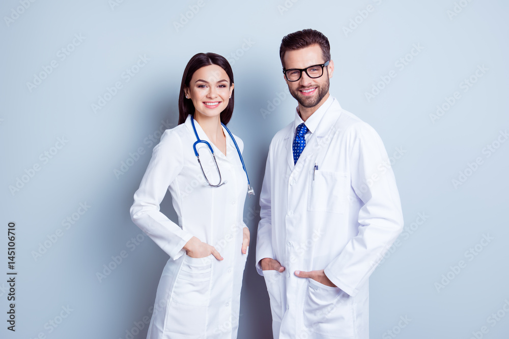 Fototapety, obrazy: Two best smart professional smiling doctors workers in white coats holding their hands in pockets and together standing against gray background